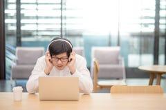 Giovane uomo asiatico che ascolta la musica nell'area di lavoro Fotografia Stock