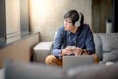 Giovane uomo asiatico che ascolta la musica sul sofà Immagine Stock