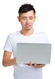 Giovane uomo asiatico che esamina computer portatile Immagini Stock Libere da Diritti