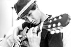 Giovane uomo asiatico che gioca chitarra spagnola all'interno fotografie stock