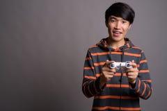 Giovane uomo asiatico che gioca contro il fondo grigio fotografia stock