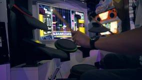 Giovane uomo asiatico che gioca il gioco dei tamburi su musica Arcade Machine Pads nel centro commerciale di zona MBK del gioco 4 archivi video