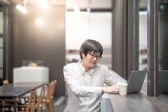 Giovane uomo asiatico che lavora con il computer portatile in caffè Immagine Stock Libera da Diritti