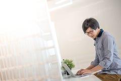 Giovane uomo asiatico che lavora con il computer portatile in caffè Fotografie Stock