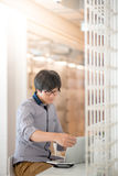 Giovane uomo asiatico che lavora con il computer portatile in caffè Fotografia Stock
