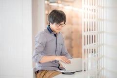Giovane uomo asiatico che lavora con il computer portatile in caffè Fotografie Stock Libere da Diritti