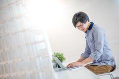 Giovane uomo asiatico che lavora con il computer portatile in caffè Immagine Stock