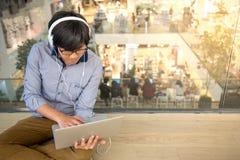 Giovane uomo asiatico che lavora con il computer portatile mentre ascoltando la musica Fotografia Stock Libera da Diritti