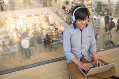 Giovane uomo asiatico che lavora con il computer portatile mentre ascoltando la musica Immagine Stock Libera da Diritti