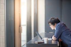Giovane uomo asiatico che lavora con il computer portatile in ufficio fotografia stock