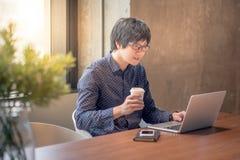 Giovane uomo asiatico che lavora con il computer portatile in ufficio Fotografia Stock Libera da Diritti