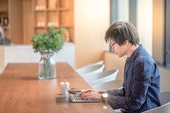 Giovane uomo asiatico che lavora con il computer portatile in ufficio Immagine Stock Libera da Diritti