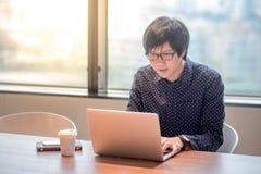 Giovane uomo asiatico che lavora con il computer portatile in ufficio Immagini Stock Libere da Diritti