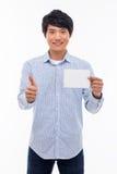 Giovane uomo asiatico che mostra carta vuota e che mostra pollice. Immagine Stock