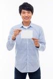 Giovane uomo asiatico che mostra carta vuota. Immagini Stock