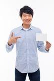 Giovane uomo asiatico che mostra carta vuota. Fotografia Stock