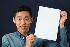 Giovane uomo asiatico che mostra la pagina bianca dello spazio della copia fotografia stock