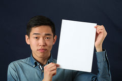 Giovane uomo asiatico che mostra la pagina bianca dello spazio della copia e che esamina camma fotografie stock