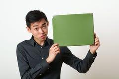 Giovane uomo asiatico che mostra la scatola verde dello spazio della copia immagine stock