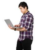 Giovane uomo asiatico che per mezzo del computer portatile Immagine Stock