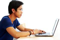Giovane uomo asiatico che per mezzo del computer portatile Immagini Stock Libere da Diritti