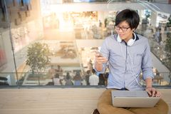 Giovane uomo asiatico che per mezzo dello smartphone e del computer portatile Fotografie Stock
