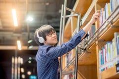 Giovane uomo asiatico che raggiunge per prenotare in biblioteca Immagini Stock Libere da Diritti
