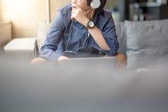 Giovane uomo asiatico che si siede sul sofà con il computer portatile Fotografia Stock Libera da Diritti