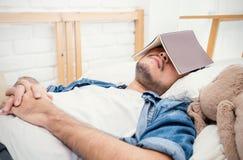 Giovane uomo asiatico che si trova a letto con il libro Immagini Stock Libere da Diritti