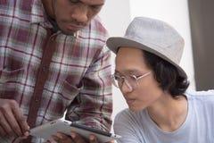 Giovane uomo asiatico con attimo sorridente di vetro e del cappello discutere qualcosa con l'amico che mostra una compressa fotografie stock libere da diritti