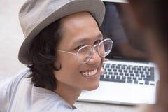 Giovane uomo asiatico con il cappello ed i vetri che sorride all'amico con il computer portatile nel fondo fotografia stock