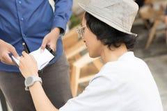 Giovane uomo asiatico con il cappello ed i vetri della fedora che scrive sulla nota per firmare una certa cosa immagini stock
