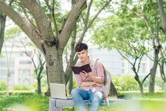 Giovane uomo asiatico con lo zaino che legge un libro Immagine Stock