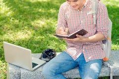 Giovane uomo asiatico con lo zaino che legge un libro Immagine Stock Libera da Diritti