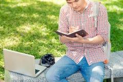 Giovane uomo asiatico con lo zaino che legge un libro Fotografia Stock