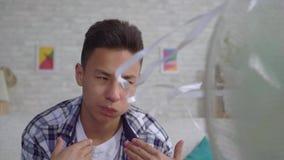 Giovane uomo asiatico conservato dal calore che si siede davanti ad un fan di lavoro il concetto della fine di calore sul Mo lent video d archivio
