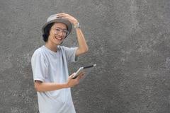 Giovane uomo asiatico creativo atractive con il cappello ed i vetri facendo uso della compressa e sorridere della fedora alla mac fotografia stock