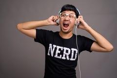 Giovane uomo asiatico del nerd che ascolta la musica contro il fondo grigio fotografie stock