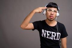 Giovane uomo asiatico del nerd che ascolta la musica contro il fondo grigio immagine stock libera da diritti