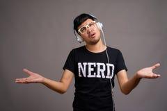 Giovane uomo asiatico del nerd che ascolta la musica contro il fondo grigio fotografia stock libera da diritti