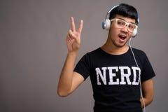 Giovane uomo asiatico del nerd che ascolta la musica contro il fondo grigio fotografie stock libere da diritti