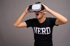 Giovane uomo asiatico del nerd facendo uso della cuffia avricolare di realtà virtuale fotografie stock libere da diritti