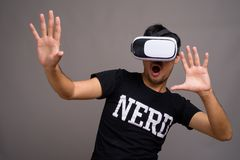 Giovane uomo asiatico del nerd facendo uso della cuffia avricolare di realtà virtuale immagine stock