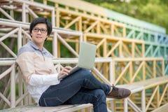 Giovane uomo asiatico dello studente che si siede sulla tribuna facendo uso del computer portatile Immagini Stock Libere da Diritti