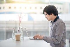 Giovane uomo asiatico di affari che lavora nella caffetteria Immagini Stock Libere da Diritti