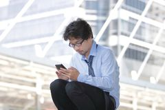 Giovane uomo asiatico disoccupato che cerca lavoro in Smart Phone mobile al fondo della città Concetto di disoccupazione immagini stock libere da diritti