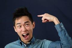Giovane uomo asiatico divertente che indica il dito indice al taglio di capelli Immagini Stock
