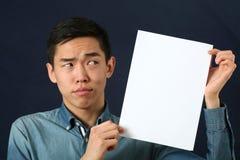 Giovane uomo asiatico divertente che mostra la pagina bianca dello spazio della copia immagine stock