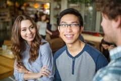 Giovane uomo asiatico e donna allegra che ascoltano il loro amico fotografia stock libera da diritti