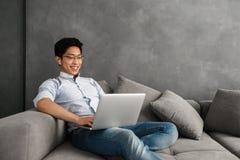 Giovane uomo asiatico felice che per mezzo del computer portatile Immagine Stock Libera da Diritti